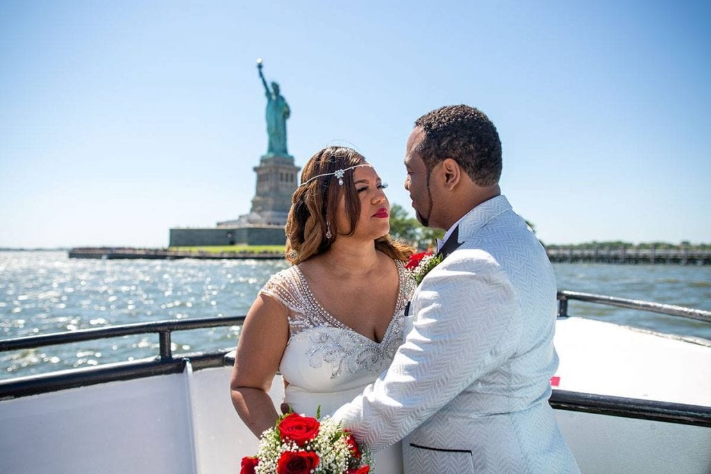 A beautiful couple in front of the Statue of Liberty