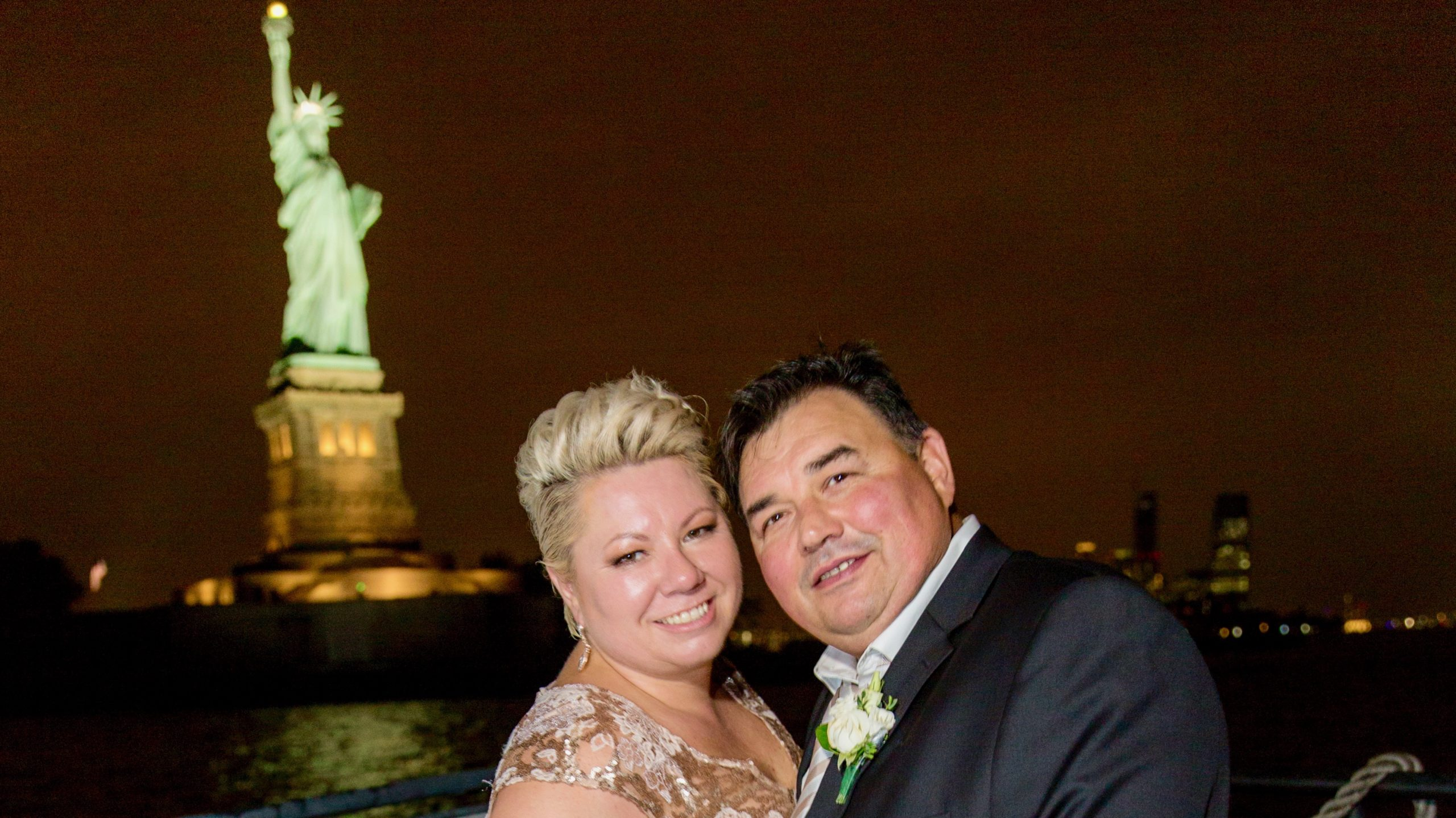 couple photo in front of statue of liberty