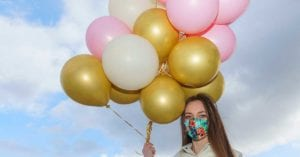 girl wearing mask holding balloons