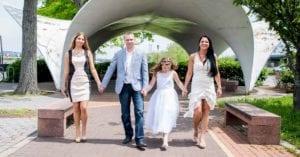 Family in formalwear walking down brick path.